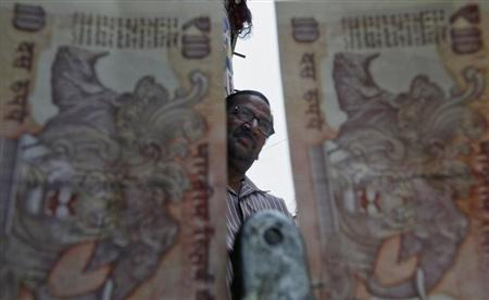 A roadside currency exchange vendor is pictured through rupee notes in the old quarters of Delhi May 31, 2013. REUTERS/Anindito Mukherjee/Files