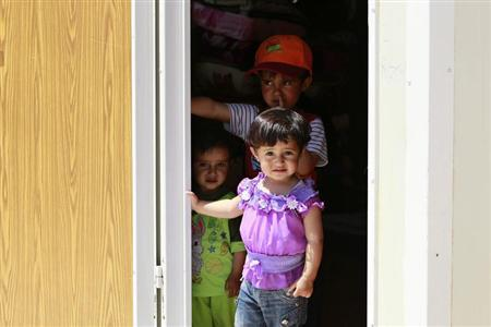 Syrian refugee children stand inside their family caravan at the Mrajeeb Al Fhood refugee camp, 20 km (12.4 miles) east of the city of Zarqa April 29, 2013. REUTERS/Muhammad Hamed