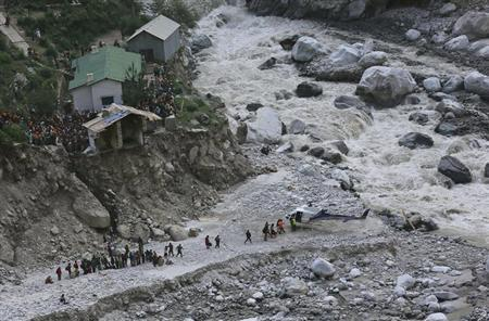 Soldiers assist survivors to board a rescue helicopter next to the River Alaknanda, during rescue operations in Govindghat in the Himalayan state of Uttarakhand June 22, 2013. REUTERS/Danish Siddiqui