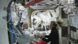 U.S. astronaut Karen Nyberg assists Italian astronaut Luca Parmitano after water began building up inside his helmet during a spacewalk outside the International Space Station, in this still image taken from NASA video July 16, 2013. REUTERS/NASA/Handout via Reuters