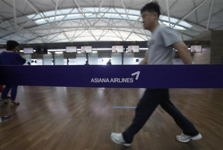 A passenger walks past a logo of Asiana Airline at the Incheon Airport in Incheon, west of Seoul July 7, 2013. REUTERS/Kim Hong-Ji