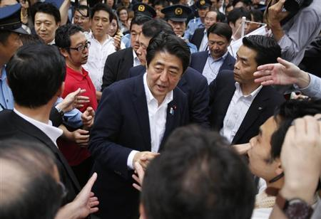 Japan's Prime Minister Shinzo Abe (C), who is also leader of the ruling Liberal Democratic Party, shakes hands with voters during his stumping tour in Tokyo July 4, 2013, at the start day of campaign the July 21 Upper house election. REUTERS/Yuya Shino