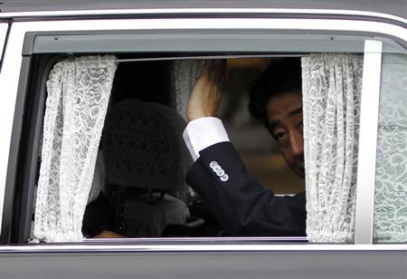 Japan's Prime Minister Shinzo Abe waves to voters from a car during his stumping tour in Tokyo July 4, 2013 file photo. REUTERS/Yuya Shino