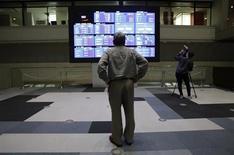Посетитель Токийской фондовой биржи смотрит на экран с рыночными котировками 20 мая 2013 года. Азиатские фондовые рынки, кроме Китая, выросли в среду за счет локальных факторов и в ожидании выступления председателя ФРС Бена Бернанке в Конгрессе. REUTERS/Toru Hanai
