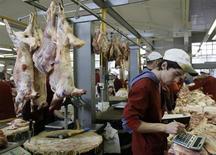 Продавец мяса считает на калькуляторе на рынке в Москве 13 октября 2008 года. Рост потребительских цен в России за неделю с 9 по 15 июля 2013 года замедлился до 0,1 процента с 0,2 процента неделей ранее, сообщил Росстат в среду. REUTERS/Denis Sinyakov