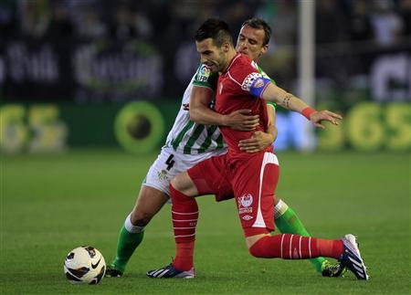 Real Betis' Antonio Amaya (rear) challenges Sevilla's Alvaro Negredo during their Spanish first division soccer match at Benito Villamarin stadium in Seville April 12, 2013. REUTERS/Marcelo del Pozo