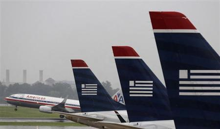 An American Airlines jet takes off while U.S. Airways jets are lined up at Reagan National Airport on the day U.S. Airways' stockholders are expected to vote on whether to approve the $11 billion merger of the two airlines effectively creating the world's largest carrier, in Washington July 12, 2013. REUTERS/Larry Downing