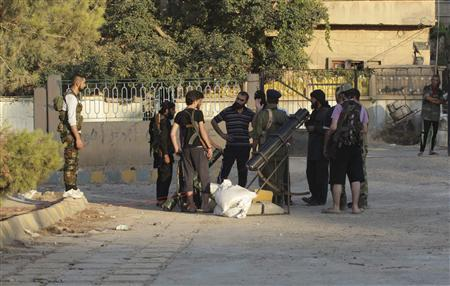 Free Syrian Army members gather on a street as they prepare an improvised rocket launcher in Deir al-Zor July 16, 2013. Picture taken July 16, 2013. REUTERS/Khalil Ashawi