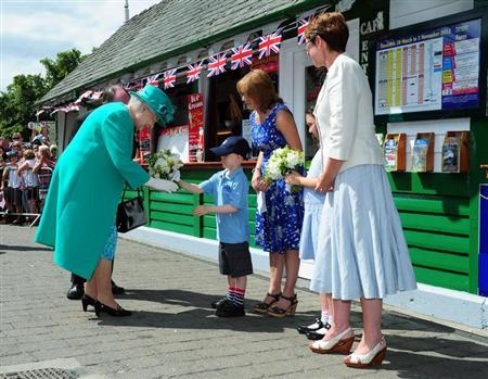 Britain's Queen Elizabeth is presented with a posy of flowers by Daniel Dixon, aged six, as she arrives at Bowness-on-Windermere Pier, in Cumbria, northern England July 17, 2013. REUTERS/Anna Gowthorpe/Pool