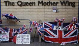 A Royal fan reads the newspaper outside St Mary's Hospital opposite the Lindo Wing, where Britain's Catherine, Duchess of Cambridge is due to give birth, in London July 17, 2013. REUTERS/Suzanne Plunkett