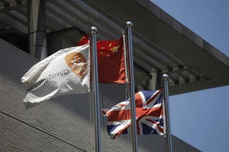 A flag (L) bearing the logo of GlaxoSmithKline (GSK) flutters next to a Chinese national flag (C) and a Union Flag (R), outside a GlaxoSmithKline office building in Shanghai July 12, 2013. REUTERS/Aly Song