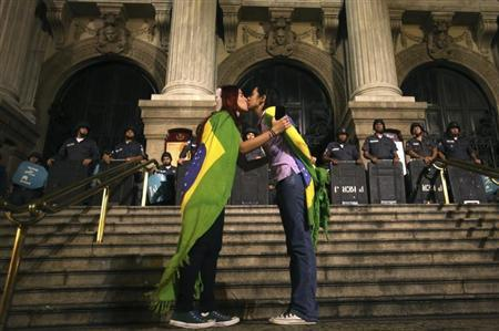 Two demonstrators kiss each other in front of police officers during a protest in central Rio de Janeiro June 27, 2013. REUTERS/Pilar Olivares