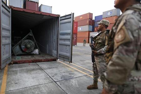 Panama police officers stand guard in front of a container holding a green missile-shaped object seized from the North Korean flagged ship ''Chong Chon Gang'' at the Manzanillo Container Terminal in Colon City July 17, 2013. REUTERS/Carlos Jasso