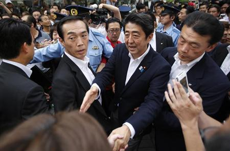 Japan's Prime Minister Shinzo Abe (2nd R), who is also leader of the ruling Liberal Democratic Party, shakes hands with voters during his stumping tour in Tokyo July 4, 2013, at the start day of campaign the July 21 Upper house election. REUTERS/Yuya Shino