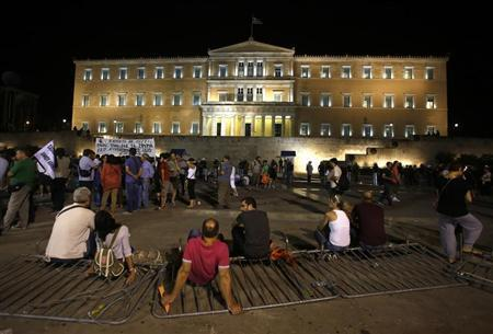 Demonstrators sit on a broken metal fence outside the Greek parliament during an anti-austerity protest in Athens, late July 17, 2013, as Greece's shaky coalition government scraped through a vote on a bill to sack public sector workers. The bill includes deeply divisive plans for a transfer and layoff scheme for 25,000 public workers - mainly teachers and municipal police - that had triggered a week of almost daily marches, rallies and strikes in protest. REUTERS/Yannis Behrakis (GREECE - Tags: POLITICS BUSINESS CIVIL UNREST EMPLOYMENT) - RTX11PV0