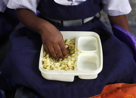 A schoolgirl eats her free mid-day meal, distributed by a government-run primary school, in New Delhi July 5, 2013. REUTERS/Mansi Thapliyal