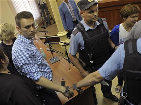 Russian protest leader Alexei Navalny (L) is handcuffed and escorted by Interior Ministry officers inside a courtroom in Kirov, July 18, 2013. REUTERS/Kommersant Photo