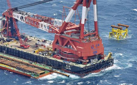 An aerial view shows a Chinese facility under construction (top R) for natural gas exploration and a large crane ship are seen near what Tokyo claims to be the median line between the overlapping exclusive economic zones of Japan and China, in the East China Sea, in this photo taken by Kyodo July 5, 2013. REUTERS/Kyodo