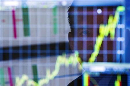 A trader looks up at a chart on his computer screen while working on the floor of the New York Stock Exchange shortly after the market opening in New York July 11, 2013. REUTERS/Lucas Jackson