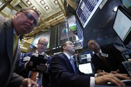 Goldman Sachs floor governor Donald Himpele (R) and specialist trader Jason Notter (2nd R) calculate the price on the initial public offering for NRG Yield Inc. on the floor at the New York Stock Exchange, July 17, 2013. REUTERS/Brendan McDermid