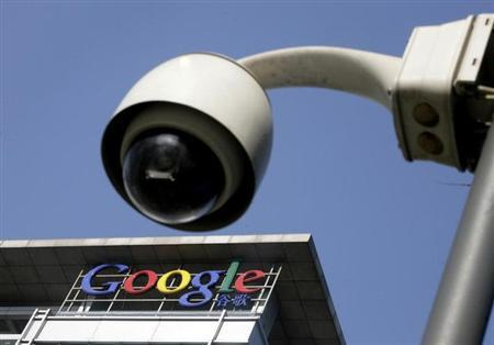 The Google logo is seen on the top of its China headquarters building behind a road surveillance camera in Beijing January 26, 2010. REUTERS/Jason Lee/Files