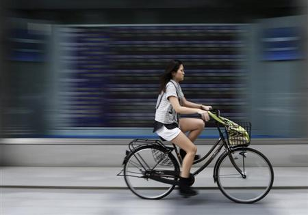 A woman cycles past a stock quotation board outside a brokerage in Tokyo June 28, 2013. REUTERS/Toru Hanai/Files