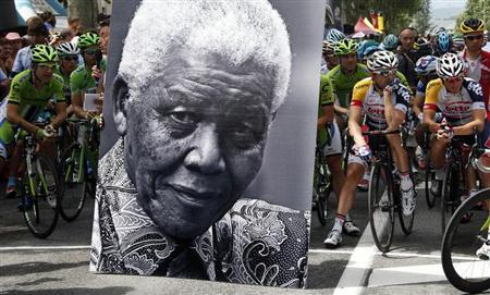 The pack of riders stands behinf a portrait as he pays respect to former South African President Nelson Mandela before the start of the 172.5km eighteenth stage of the centenary Tour de France cycling race from Gap to l'Alpe d'Huez, in the French Alps, July 18, 2013. REUTERS/Eric Gaillard
