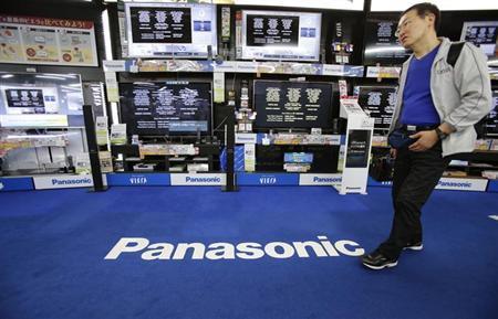 A man walks past Panasonic Corp's Viera televisions displayed at an electronics store in Tokyo May 9, 2013. REUTERS/Toru Hanai/Files