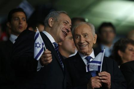 Israel's Prime Minister Benjamin Netanyahu and Israeli President Shimon Peres (R) smile as they hold Israeli flags during the opening ceremony of the 19th Maccabiah Games at Teddy Stadium in Jerusalem July 18, 2013. REUTERS/Baz Ratner