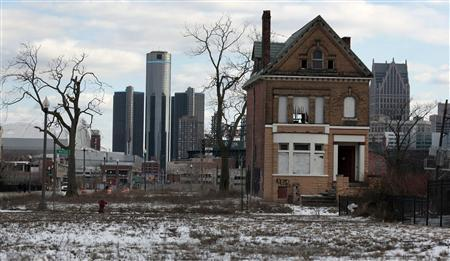 A vacant, boarded up house is seen in the once thriving Brush Park neighbourhood with the downtown Detroit skyline behind it in Detroit, Michigan in this March 3, 2013 file photo. REUTERS/Rebecca Cook/Files