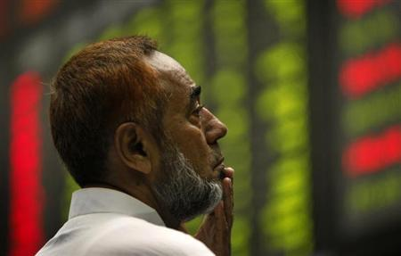 An investor, with henna-dyed hair, monitors an electronic board displaying stock prices at Karachi Stock Exchange July 16, 2010. REUTERS/Akhtar Soomro/Files