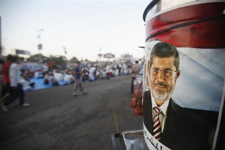 A poster of deposed Egyptian President Mohamed Mursi is seen as his supporters wait to break fast on the first day of Ramadan at the Rabaa Adawiya square where they are camping in Cairo July 10, 2013. REUTERS/Khaled Abdullah