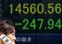 A woman walks past a stock quotation board displaying Japan's Nikkei average outside a brokerage in Tokyo July 19, 2013. REUTERS/Toru Hanai