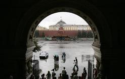 Люди укрываются от дождя у входа в ГУМ в Москве 7 августа 2007 года. Выходные в Москве будут прохладными и ненастными, ожидают синоптики. REUTERS/Denis Sinyakov