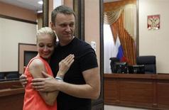 Оппозиционный лидер Алексей Навальный обнимает жену Юлию в зале суда в Кирове, освободившего его из-под стражи под подписку о невыезде 19 июля 2013 года. Навальный поблагодарил за это тысячи москвичей и жителей других городов, вышедших на улицы поддержать оппозиционного лидера и кандидата в мэры столицы. REUTERS/Sergei Karpukhin