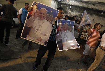 A man sells posters with the Pope's photo during the visit of the World Youth Day cross in the Rocinha slum in Rio de Janeiro July 18, 2013. REUTERS/Pilar Olivares
