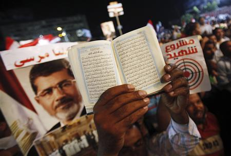 A copy of the Koran is held up near a poster of deposed Egyptian President Mohamed Mursi during a rally by members of the Muslim Brotherhood and Mursi supporters at the Rabaa Adawiya square where they are camping, in Cairo July 18, 2013. REUTERS/Amr Abdallah Dalsh
