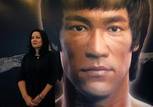Shannon Lee, daughter of the late Kung Fu legend Bruce Lee, poses in front of a portrait of her father at the Hong Kong Heritage Museum, before the start of a five-year exhibition on Lee, July 18, 2013. REUTERS/Bobby Yip