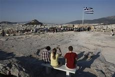 Tourists take photographs at the top of the Acropolis hill in Athens July 4, 2013. REUTERS/John Kolesidis
