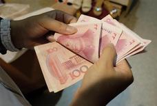 Женщина считает юани на рынке в Пекине 1 июля 2013 года. Центробанк Китая в пятницу объявил о долгожданных реформах процентной ставки, отменив нижний предел ставок, по которым банки кредитуют клиентов. REUTERS/Jason Lee