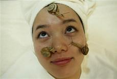 Snails crawl on the face of a woman during a demonstration of a new beauty treatment at Clinical-Salon Ci:z.Labo in central Tokyo July 17, 2013. REUTERS/Issei Kato