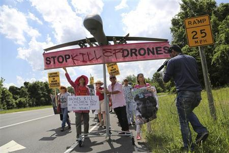 Protesters against drone strikes walk along the highway with a model of a drone in an attempt to deliver a letter to U.S. Central Intelligence Agency (CIA) Director John Brennan as they gather outside CIA headquarters in Langley, Virginia, June 29, 2013. REUTERS/Jonathan Ernst