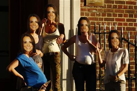 Women pretending to be pregnant and wearing masks of Britain's Catherine, Duchess of Cambridge pose outside the Lindo Wing of St Mary's Hospital, where the Duchess of Cambridge is expected to give birth, in London July 18, 2013. REUTERS/Luke MacGregor