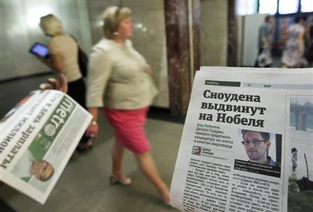 An employee distributes newspapers, with a photograph (R) of former U.S. spy agency contractor Edward Snowden seen on a page, at an underground walkway in central Moscow July 2, 2013. REUTERS/Maxim Shemetov