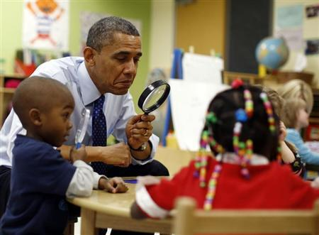 U.S. President Barack Obama uses a magnifying glass to play a game with children in a pre-kindergarten classroom at College Heights early childhood learning center in Decatur February 14, 2013. REUTERS/Jason Reed