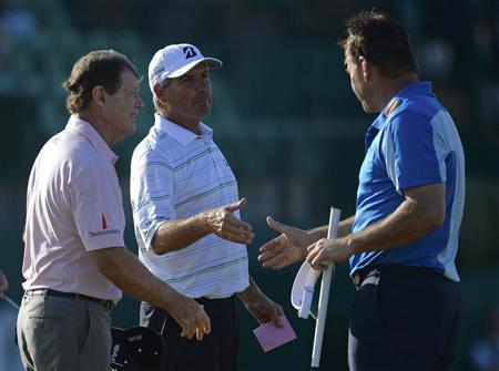 Tom Watson (L) and Fred Couples of the U.S. shake hands with Nick Faldo of England (R) on the 18th green as they finish their second round of the British Open golf Championship at Muirfield in Scotland July 19, 2013. REUTERS/Russell Cheyne