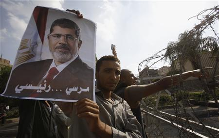 A member of the Muslim Brotherhood and supporter of deposed Egyptian President Mohamed Mursi holds up a poster of Mursi behind barbed wires outside the Republican Guard headquarters in Cairo July 19, 2013. REUTERS/Amr Abdallah Dalsh