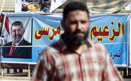 A man walks near a poster of former Egyptian President Mohamed Mursi in Assiut July 14, 2013. REUTERS/Mohamed Abd El Ghany