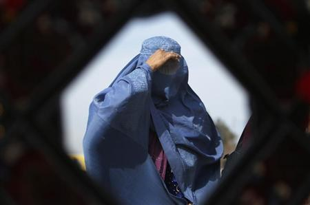 An Afghan woman is reflected in a mirror as she walks in Kabul February 11, 2013. REUTERS/Mohammad Ismail