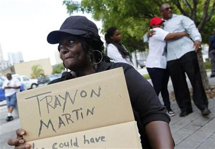 Denise Richardson, of Miami, holds a sign before a rally led by Tracy Martin, father of Trayvon Martin, in Miami, Florida July 20, 2013. REUTERS-Andrew Innerarity